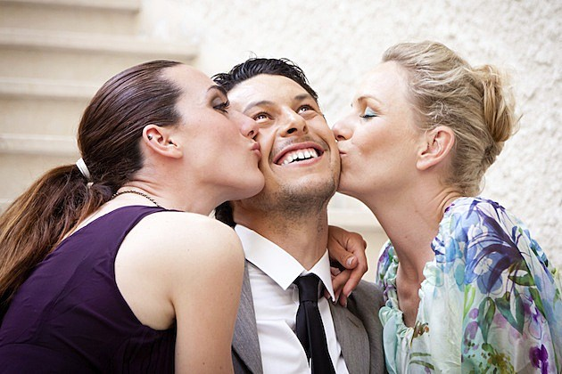 Two women kissing man