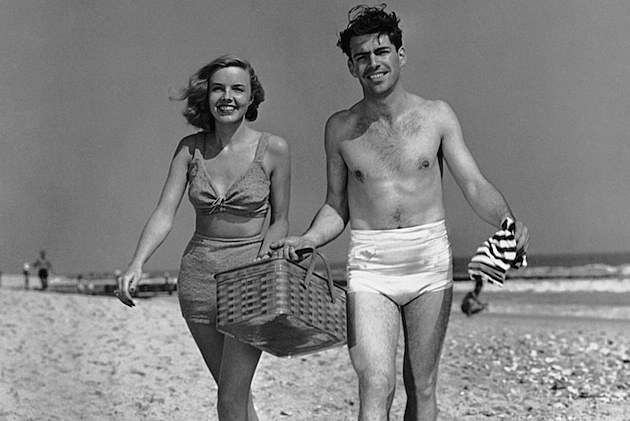 Couple walking with picnic basket on beach